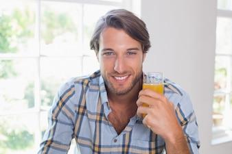Casual smiling man having orange juice