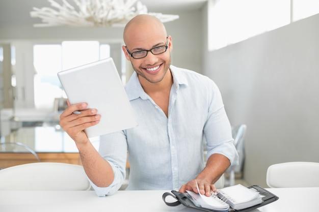 Случайный улыбающийся человек с цифровой планшета и дневник дома