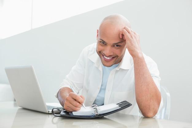 Случайные улыбающийся человек с ноутбуком, писать в дневник дома