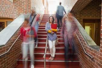 Casual smiling student standing on stairs