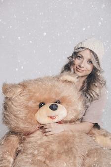 雪の背景に大きな柔らかいテディベアを保持しているニット服でカジュアルな笑顔の若い女性