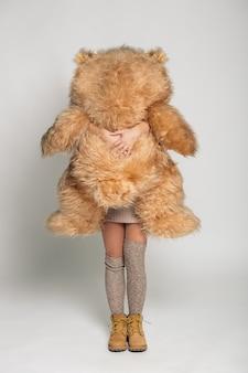 大きな柔らかいテディベアを保持しているニット服でカジュアルな笑顔の若い女性