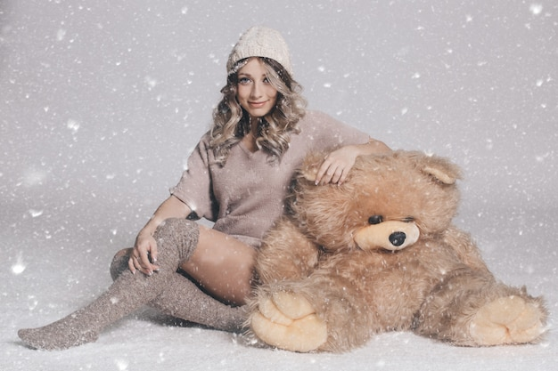 Casual smiling young woman in knitted clothes holding big soft teddy bear on snowy background