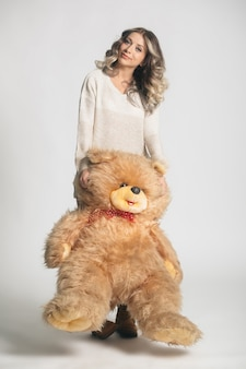 Casual smiling young woman in knitted clothes holding big soft teddy bear