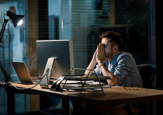 Casual stressed worker late in office