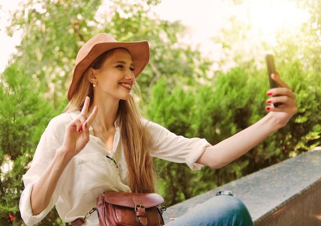 都市公園に座って屋外で自分撮りをしているフェルト帽子のカジュアルなスタイルの金髪