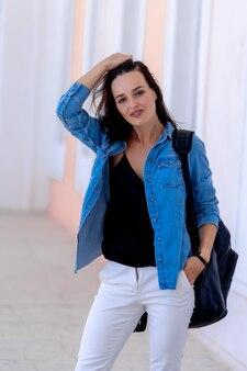 バックパックとカジュアルなスタイルの女性。青いシャツと白いジーンズに身を包んだ若い女性のビュー。カメラを見てください。