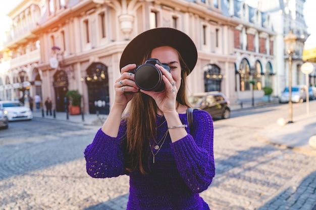Повседневная стильная женщина-фотограф в шляпе с камерой dslr, делающая фотографии во время путешествия по европейскому городу