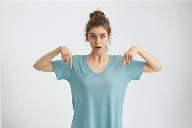 Случайно удивленная женщина, указывая пальцами вниз