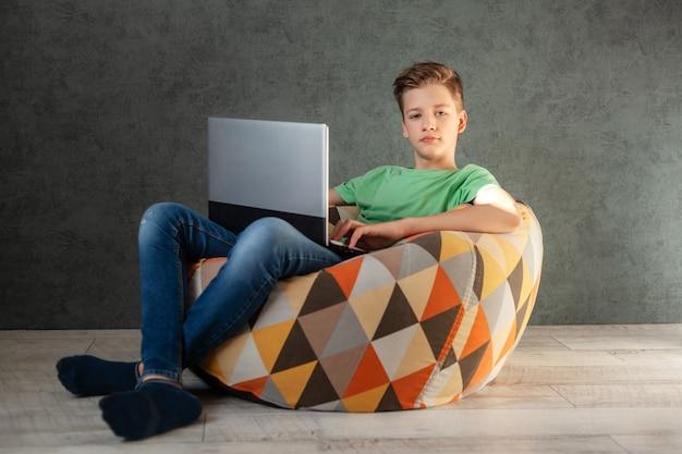自宅でビーンバッグの椅子で休んでいるラップトップを持つカジュアルな10代の少年。
