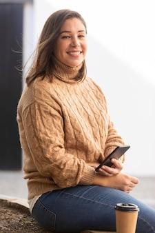 彼女の携帯電話を保持しているカジュアルなティーンエイジャー