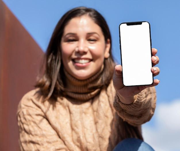 彼女のスマートフォンを保持しているカジュアルなティーンエイジャー