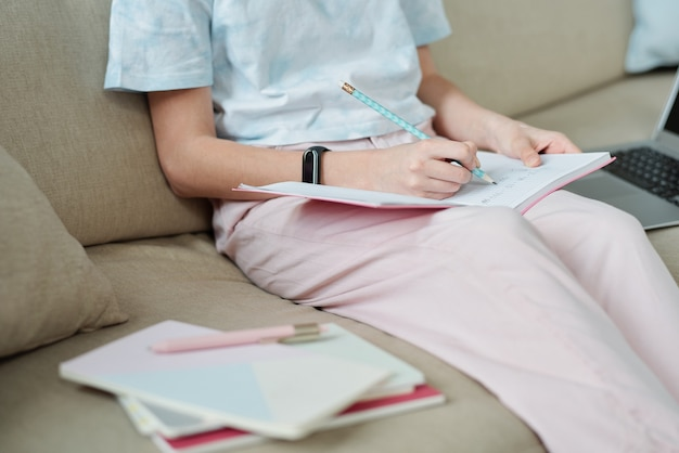 Casual teenager with open copybook and pencil sitting on couch and making notes during preparation of home assignment