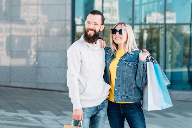 Casual urban shopping couple retail sale lifestyle smiling man and woman with paper bags