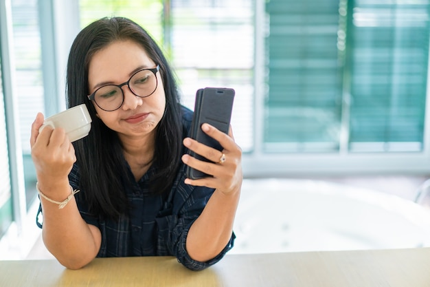 Casual woman boring talking over mobile phone with coffee cup on hand