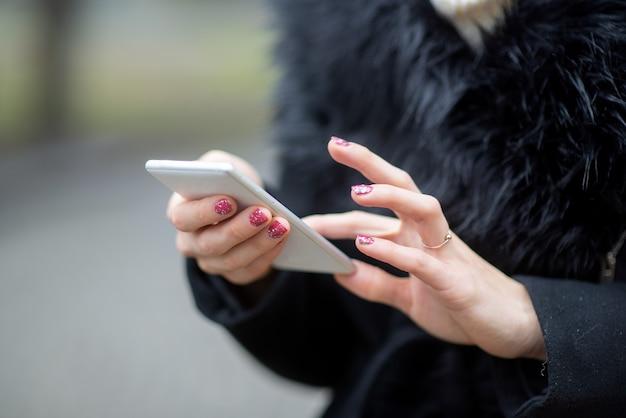 도시 거리 배경에서 휴대 전화를 사용하는 캐주얼 여성 손