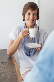 Casual woman having a coffee with friend