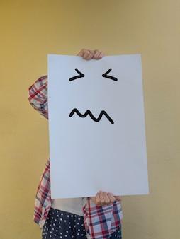 非常に怒った顔で空白の看板の後ろに彼女の顔を隠すカジュアルな女性コピースペース