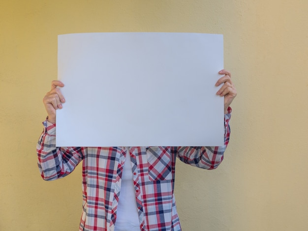Casual woman hiding her face behind a blank billboard. copy space