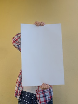 Casual woman hiding her face behind a blank . copy space