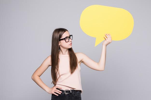 Вскользь женщина держа пузырь речи изолированный на белой стене