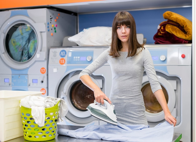 Вскользь женщина гладит одежду среднего выстрела