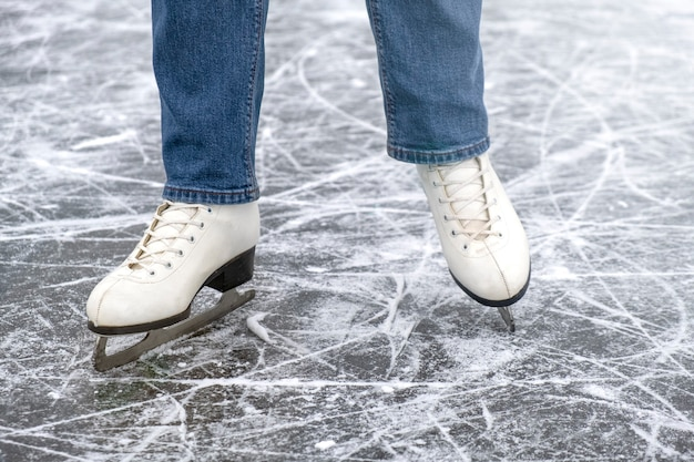 Casual woman look in ice skates and jeans on ice
