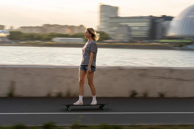 중년의 캐주얼 여성은 저녁에 강 옆 흐릿한 도시에서 롱보드에서 스케이트를 즐기며 휴식을 취합니다.
