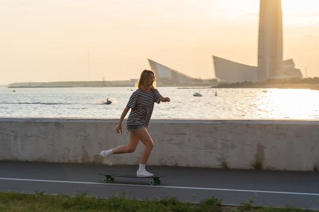 중년의 캐주얼 여성은 저녁에 강 옆 흐릿한 도시에서 롱보드에서 스케이트를 즐기며 휴식을 취합니다. 프리미엄 사진