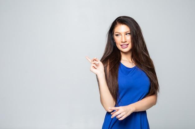 Casual woman pointing to the side and smiling isolated