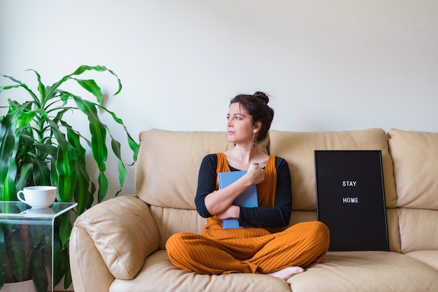Casual woman sit on the couch in her house. stay home concept. pandemic virus disease coronavirus covid 19.