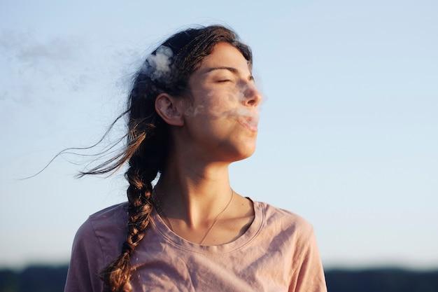 Повседневная женщина курит и закрывает глаза