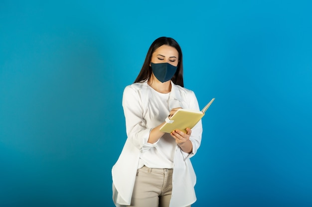 Casual woman student in medical mask writing in notepad while standing isolated on blue