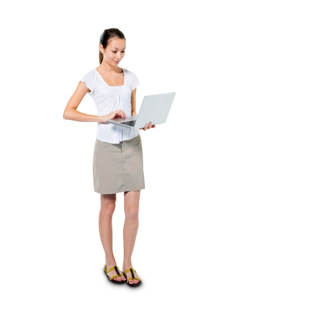 A casual woman using her laptop while standing