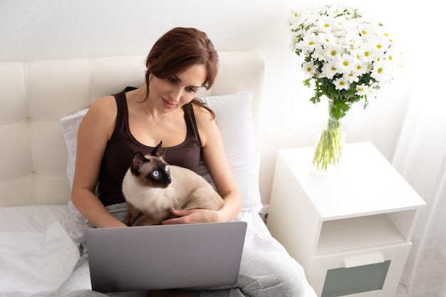 Casual woman using laptop with her siamese cat in bedroom with flowers. life with pet.