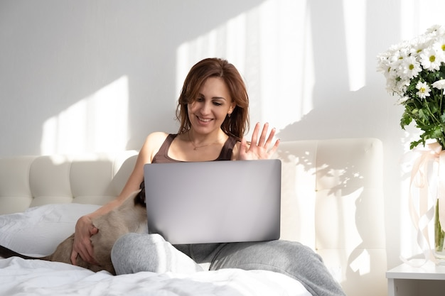 Casual woman using laptop with her siamese cat in white bedroom