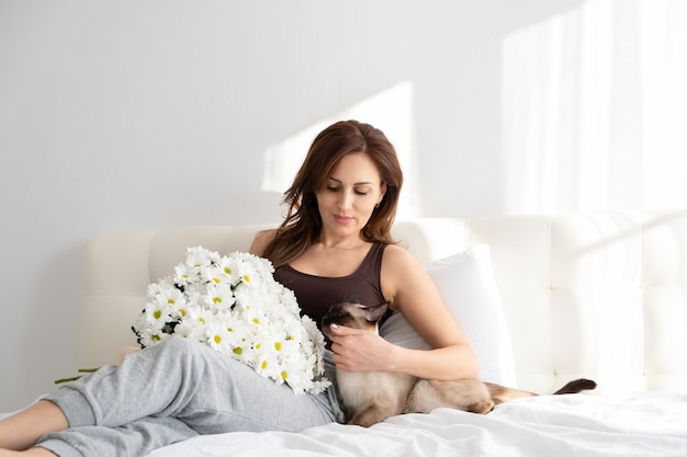 Casual woman with flowers and her siamese cat in bedroom with flowers. life with pet. shadows.