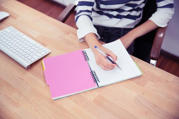 メモを書くカジュアルな女性
