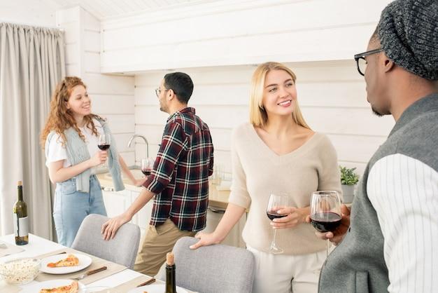 彼と話している間笑顔でアフリカの男を見ているワインのグラスを持つカジュアルな若いブロンドの女性