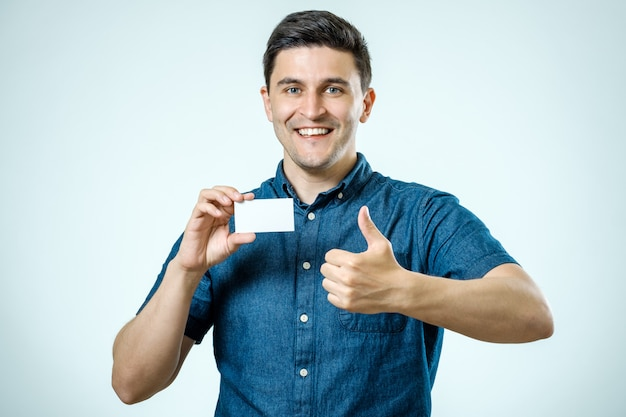 Casual young businessman holding business card