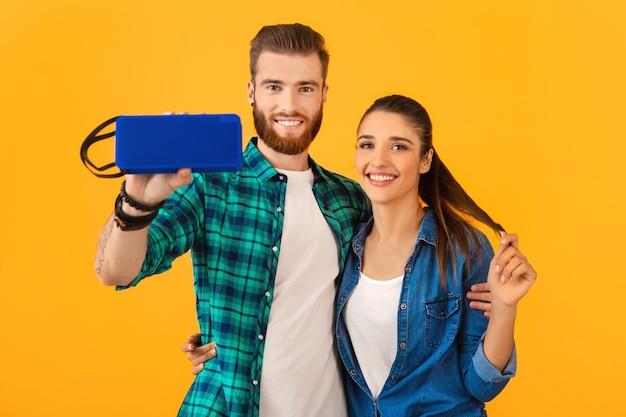 Giovani coppie casuali che tengono altoparlante senza fili felice che ascolta la musica che balla l'umore felice di stile variopinto isolato sulla parete gialla