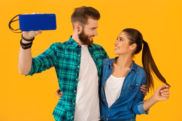 Casual young couple holding wireless speaker happy listening to music dancing colorful style happy mood isolated on yellow wall