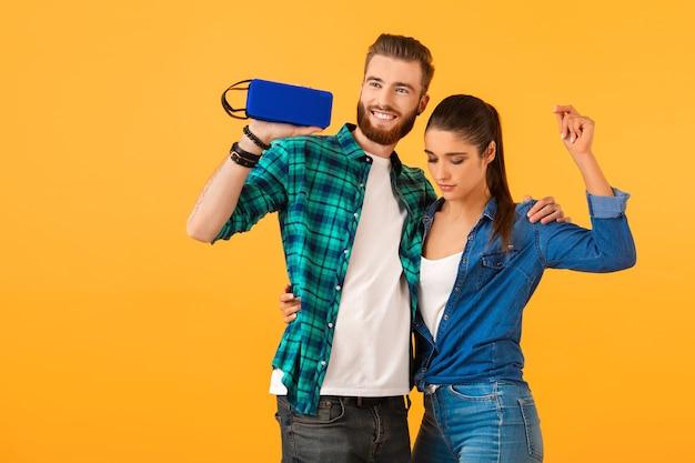 Повседневная молодая пара, держащая беспроводной динамик, счастлива слушать музыку, танцевать красочный стиль, счастливое настроение, изолированную на желтой стене