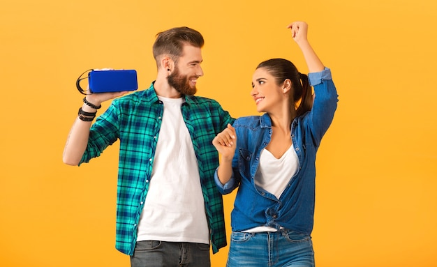 Casual young couple holding wireless speaker listening to music dancing on orange