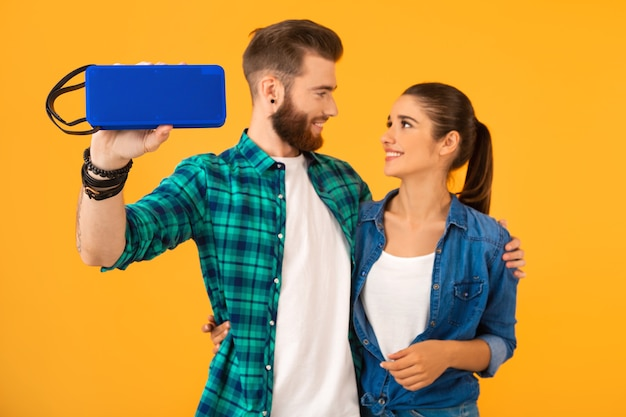 Casual young couple holding wireless speaker listening to music dancing