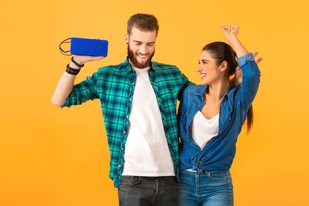 ダンス音楽を聴いてワイヤレス スピーカーを保持しているカジュアルな若いカップル