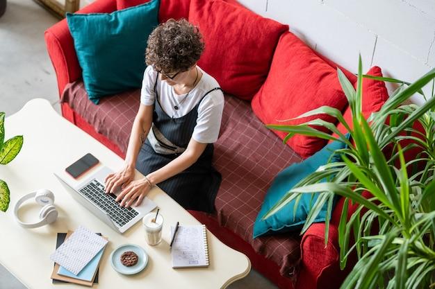 ラップトップの前のソファに座ってカジュアルな若い女性がリモートで作業しながらネットでタイピングとサーフィンをする