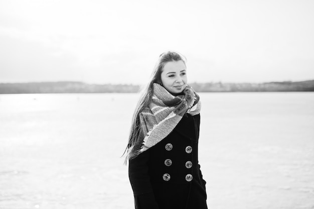 Casual young girl at black coat, and scarf against frozen river on sunny winter weather.