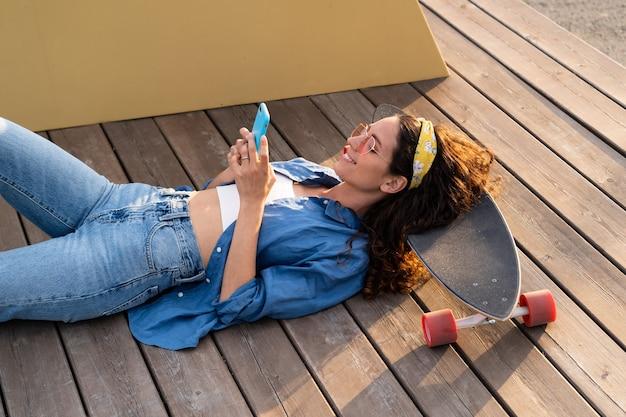야외에서 스마트폰으로 문자 메시지를 보내는 선글라스를 쓴 캐주얼 젊은 힙스터 소녀는 롱보드에 편안하게 누워 있습니다.