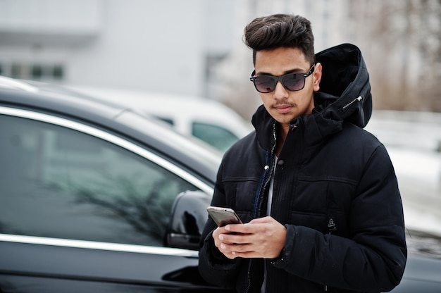 Casual young indian man in black jacket and sunglasses posed against suv car with phone at hands.